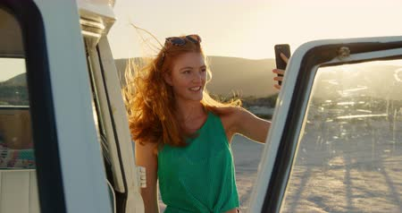 roadtrip : Front view of a young Caucasian woman enjoying free time taking a selfie by a campervan on a sunny beach by the sea Stock Footage