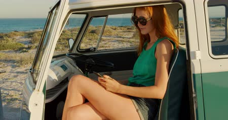 roadtrip : Side view of a young Caucasian woman enjoying free time using a smartphone in a campervan on a sunny beach by the sea