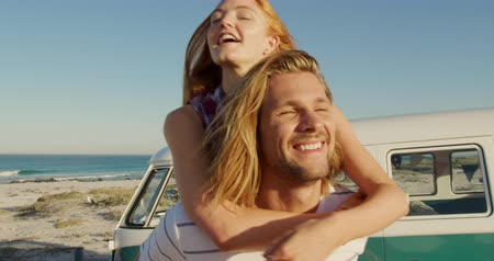 roadtrip : Front view close up of a young Caucasian man and woman enjoying free time by a campervan on a sunny beach by the sea, the man carrying the woman piggyback