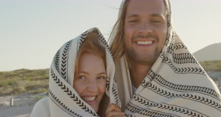 roadtrip : Portrait of a young Caucasian man and woman enjoying free time wrapped in a blanket by a campervan on a sunny beach by the sea
