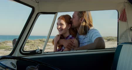 roadtrip : Side view of a young Caucasian man and woman enjoying free time by a campervan on a sunny beach by the sea