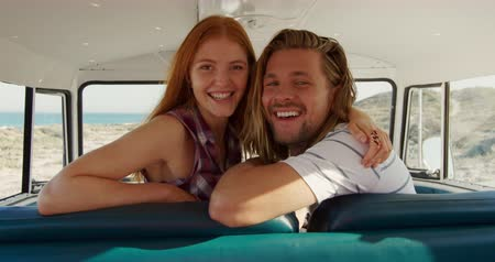 bronzeada : Portrait of a young Caucasian man and woman enjoying free time sitting in a campervan on a sunny beach by the sea, smiling to camera