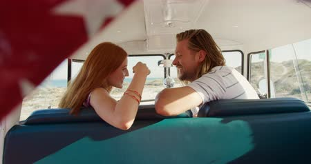 camionnette : Side view of a young Caucasian man and woman enjoying free time sitting in a campervan on a sunny beach by the sea