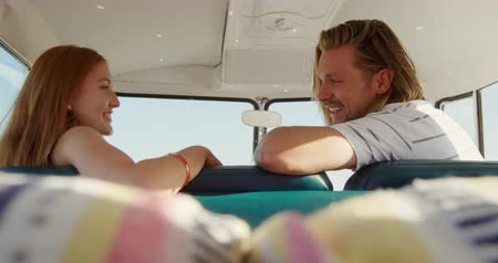 Деятельность выходные : Side view of a young Caucasian man and woman enjoying free time sitting in a campervan on a sunny beach by the sea
