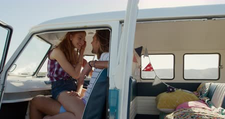 off : Side view of a young Caucasian man and woman enjoying free time kissing in a campervan on a sunny beach by the sea, the woman sitting on a lap of the man Stock Footage