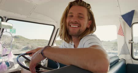 дубленый : Portrait of a young Caucasian man enjoying free time sitting in a campervan on a sunny beach by the sea, smiling to camera Стоковые видеозаписи