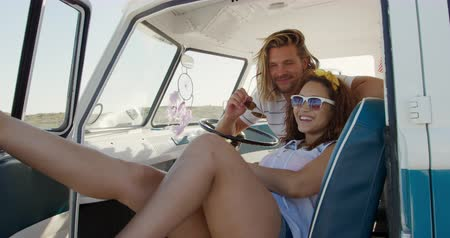 roadtrip : Front view of a young Caucasian man and a young mixed race woman enjoying free time sitting in a campervan on a sunny beach by the sea