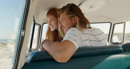 roadtrip : Side view of a young Caucasian man and woman enjoying free time sitting in a campervan on a sunny beach by the sea