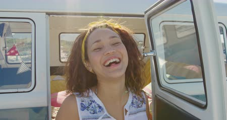roadtrip : Portrait of a young mixed race woman enjoying free time sitting in a campervan on a sunny beach by the sea, smiling to camera Stock Footage