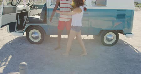 roadtrip : Front view of a young African American man and a young mixed race woman enjoying free time embracing by a campervan on a sunny beach by the sea