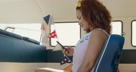 roadtrip : Side view of a young mixed race woman enjoying free time using a smartphone in a campervan on a sunny beach by the sea