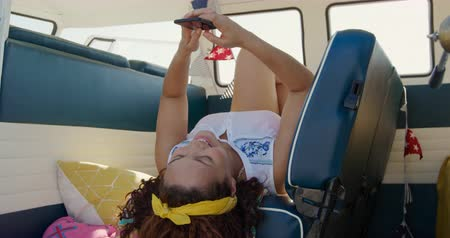 roadtrip : Front view of a young mixed race woman enjoying free time using a smartphone in a campervan on a sunny beach by the sea, taking a selfie
