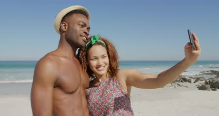 roupa de praia : Side view of a young African American man and a young mixed race woman enjoying free time using a smartphone on a sunny beach by the sea, taking a selfie