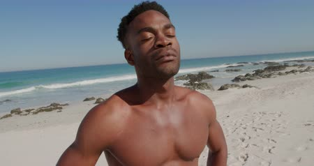Деятельность выходные : Front view close up of young African American man enjoying free time on a sunny beach by the sea, eyes closed