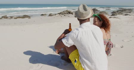companheiro : Side view of a young African American man and a young mixed race woman enjoying free time drinking beer on a sunny beach by the sea