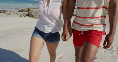 bronzeada : Front view mid section of a young African American man and a young mixed race woman enjoying free time walking on a sunny beach by the sea