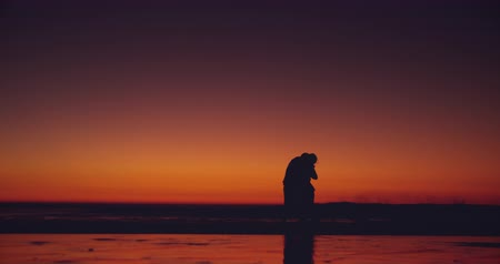 companheiro : Front view of a young couple in silhouette embracing and running on a beach at sunset