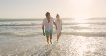 leisure time : Front view of a young mixed race couple enjoying free time running on a sunny beach by the sea