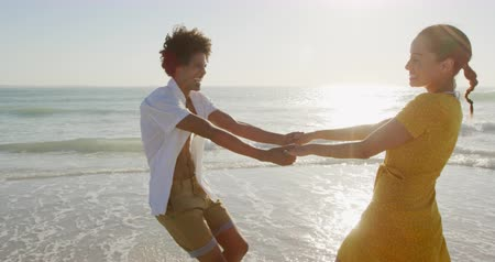 roupa de praia : Front view of a young mixed race couple enjoying free time dancing on a sunny beach by the sea Vídeos