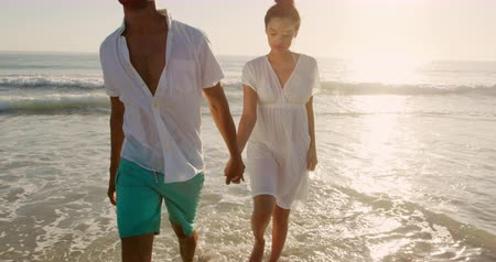 Деятельность выходные : Front view of a young mixed race couple enjoying free time walking on a sunny beach by the sea