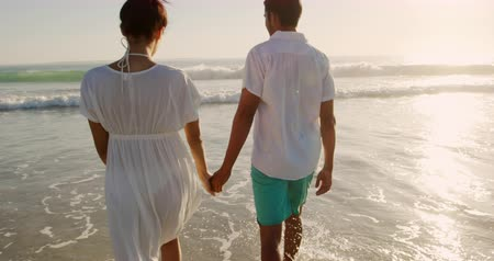 пляжная одежда : Rear view of a young mixed race couple enjoying free time walking into the sea on a sunny beach