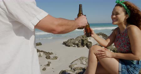 companheiro : Side view of a young Caucasian couple enjoying free time drinking beer on a sunny beach by the sea