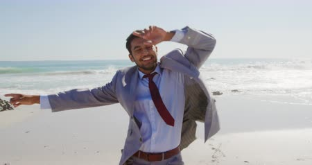 tendo : Front view of a young mixed race businessman enjoying free time dancing on a sunny beach by the sea