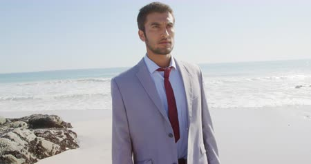 Деятельность выходные : Front view of a young mixed race businessman enjoying free time walking on a sunny beach by the sea