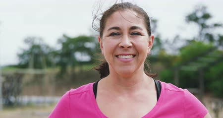 réalisations : Close up portrait of a happy Caucasian woman standing at boot camp, looking to camera and smiling, wearing a pink t shirt, in slow motion Vidéos Libres De Droits