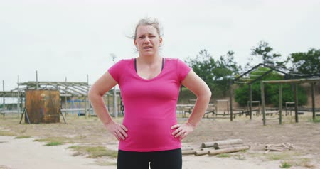 competidores : Portrait of a Caucasian woman standing at boot camp, looking to camera with hands on her hips, wearing a pink t shirt, in slow motion Archivo de Video