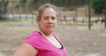 feliz : Portrait close up of a confident Caucasian woman standing at boot camp, looking to camera and smiling, wearing a pink t shirt, in slow motion Stock Footage