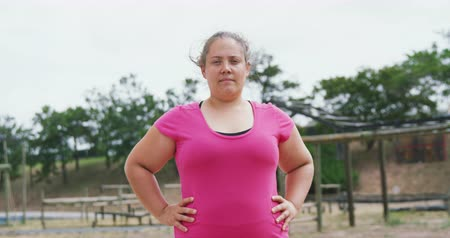 konkurenti : Portrait of a confident Caucasian woman standing at boot camp, looking to camera with hands on her hips, wearing a pink t shirt, in slow motion