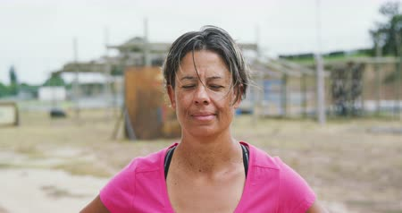 deneme : Portrait close up of a mixed race woman standing at boot camp, looking to camera and smiling, wearing a pink t shirt, in slow motion