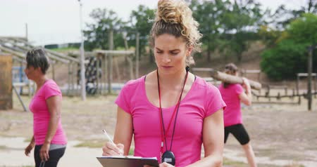 cronômetro : Front view close up of a Caucasian female coach standing at boot camp, writing on a clipboard and looking up to camera, with multi-ethnic group of female friends exercising in the background, all wearing pink t shirts, in slow motion Stock Footage