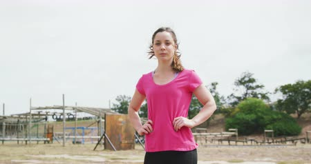 hindernis : Portrait of a Caucasian woman standing at boot camp, looking to camera with hands on her hips, wearing a pink t shirt, in slow motion Videos