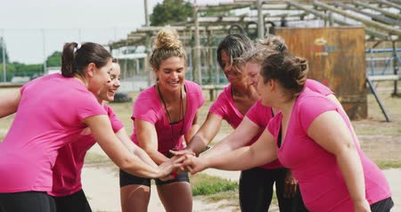 empilhamento : Front view close up of a Caucasian female coach standing at boot camp holding a tablet, motivating and stacking hands with a multi-ethnic group of female friends, in slow motion Vídeos