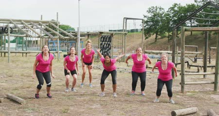 emelt : Front view of a happy multi-ethnic group of female friends enjoying exercising at boot camp together, jumping in the air in unsion with raised arms, looking to camera and smiling, all wearing pink t shirts, in slow motion Stock mozgókép