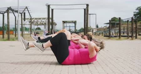 konkurenti : Side view of a happy multi-ethnic group of female friends enjoying exercising at boot camp together, training and stretching in slow motion