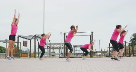 konkurenti : Side view of a happy multi-ethnic group of women enjoying exercising at boot camp together, doing burpees, all wearing pink t shirts, in slow motion