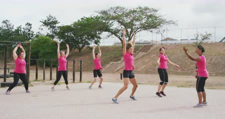 working together : Side view of a happy multi-ethnic group of female friends enjoying exercising at boot camp together, wearing pink t shirts, doing jumoing jacks with a mixed race female coach motivating them, in slow motion Stock Footage