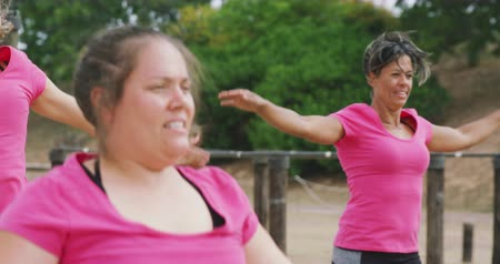 konkurenti : Side view of a happy multi-ethnic group of women enjoying exercising at boot camp together, wearing pink t shirts and doing jumping jacks, in slow motion