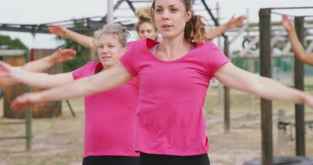 deneme : Front view of a happy multi-ethnic group of women enjoying exercising at boot camp together, wearing pink t shirts and doing jumping jacks, in slow motion
