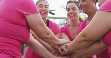 empilhamento : Low angle side view of a happy multi-ethnic group of female friends enjoying exercising at boot camp together, stacking hands, raising hands in the air and smiling, in slow motion