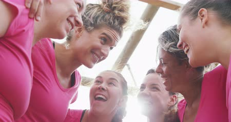 負け : Low angle side view of a happy multi-ethnic group of female friends enjoying exercising at boot camp together, embracing each other and smiling in slow motion 動画素材
