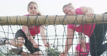 deneme : Low angle view of two happy Caucasian women enjoying exercising at boot camp together, climbing on nets to the top of a climbing frame, in slow motion