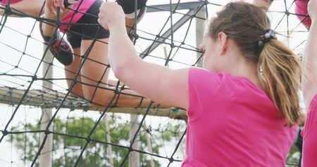 konkurenti : Low angle rear view of multi-ethnic group of women enjoying exercising at boot camp together, climbing on nets on a climbing frame, in slow motion