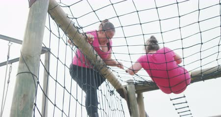 deneme : Low angle side view of a Caucasian and a mixed race woman enjoying exercising at boot camp together, climbing on nets over a climbing frame, in slow motion