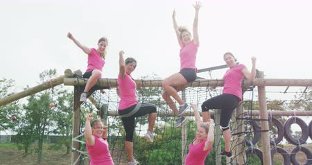 emelt : Front view of a happy multi-ethnic group of female friends enjoying exercising at boot camp together, on a climbing frame, smiling and looking to camera, sitting on climbing frame with raised arms, flexing biceps and shaking fists, in slow motion