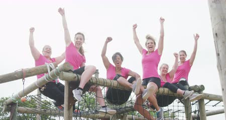 torcendo : Front view of a happy multi-ethnic group of female friends enjoying exercising at boot camp together, sitting on climbing frame with raised arms, cheering, smiling and looking to camera, in slow motion