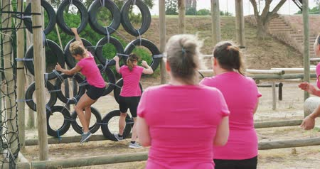 負け : Rear view of a happy multi-ethnic group of female friends enjoying exercising at boot camp together, climbing on tyres and running in slow motion